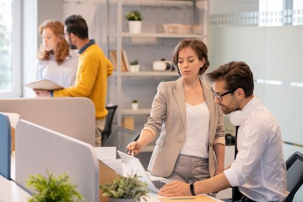 プレゼンテーションを一緒に議論するビジネス人々:若い男性に情報を説明しながらノートパソコンの画面を指して経験豊富な女性プロジェクトマネージャー Premium写真