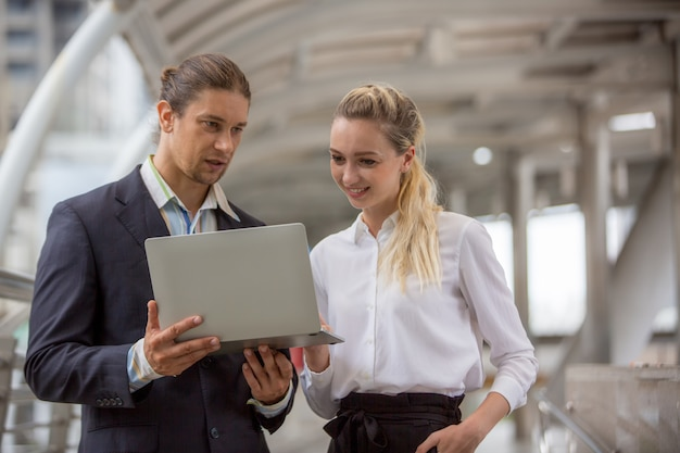 Business people discussing while standing on footbridge Premium Photo