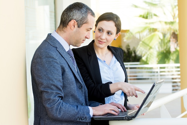 Business people discussing work using a laptop outside the office Premium Photo