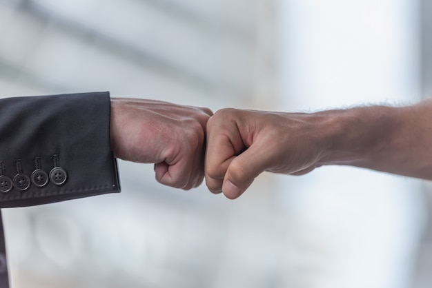 Business people giving fist bump together in teamwork at the office. Premium Photo