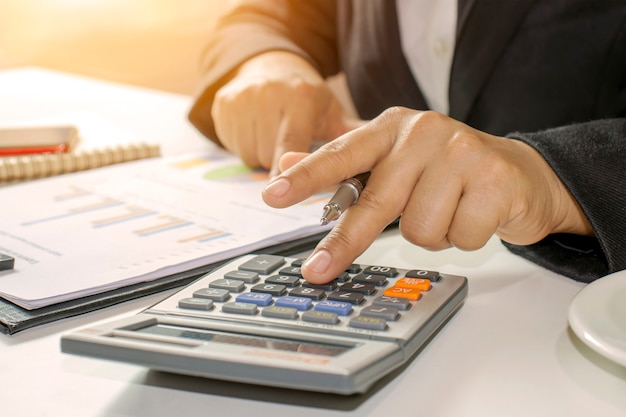 Business people hold pen to press calculator accounting ideas. Premium Photo