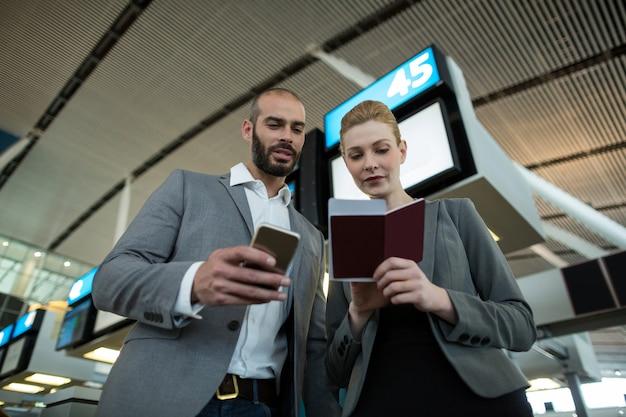 搭乗券を持って携帯電話を使うビジネスマン 無料写真