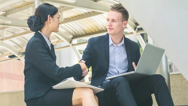 비즈니스 사람들이 숙녀와 스마트 폰과 커피 한잔 백인 똑똑한 사람과 노트북에 프레젠테이션을 이야기하고 악수 프리미엄 사진