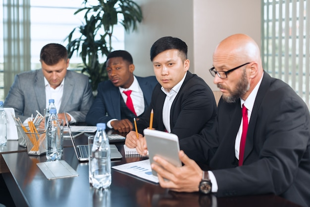 Business people meeting around a boardroom table discussing strategy Premium Photo