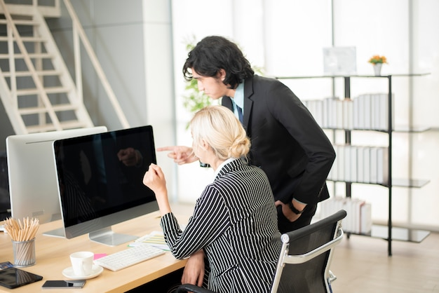 Business people pointing at computer screen Premium Photo