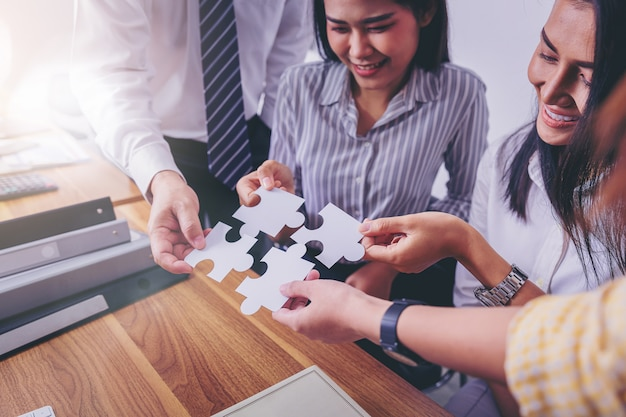 Business people putting connect jigsaw puzzle. team work and strategic solution concept. Premium Photo