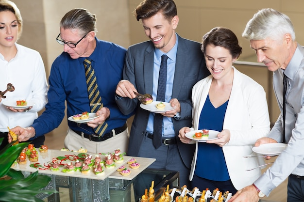 Business People Serving Themselves in Buffet Free Photo