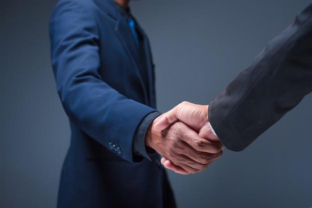 Деловые люди пожимают друг другу руки в офисе Premium Фотографии