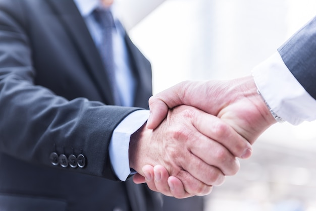 Business people shaking hands, greeting deal concept, modern city background. Premium Photo