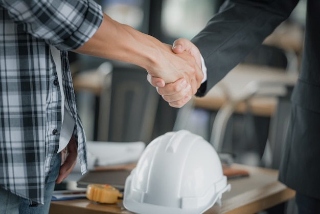 Business people shaking hands together above desk. Premium Photo
