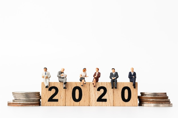 Business people sitting on wooden block number 2020 Premium Photo