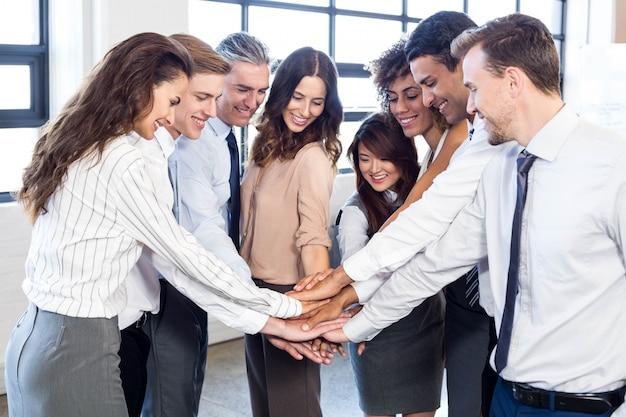 Business people stacking hands and smiling in office Premium Photo