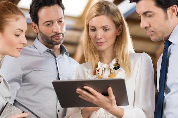 Business people standing in the office and looking at a digital tablet. Premium Photo