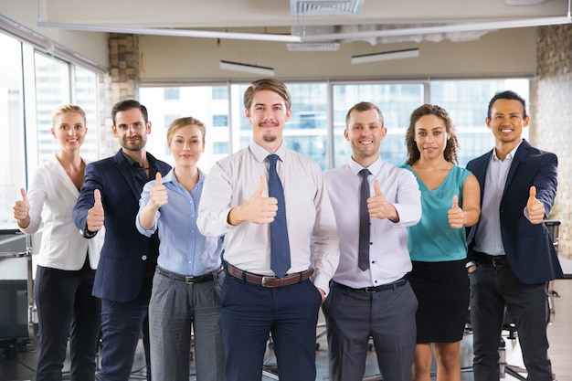 Business people standing in a row with thumbs up Free Photo