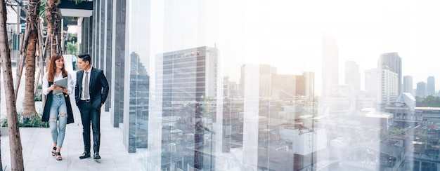 Business people walking in business district and talking about new business collaboration new event project. panoramic banner city background Premium Photo