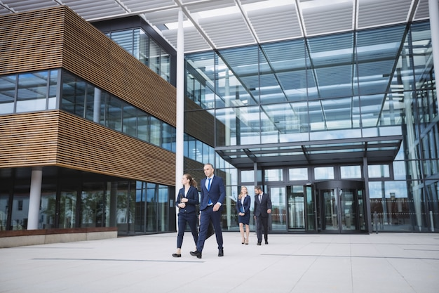 Business people walking outside office building Free Photo