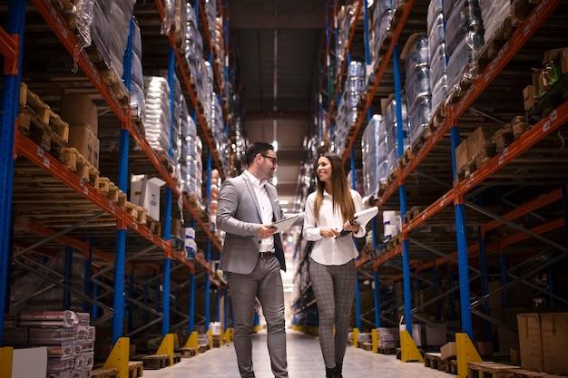 Uomini d'affari che camminano attraverso i grandi centri di distribuzione e parlano di aumentare la produzione e l'organizzazione Foto Gratuite