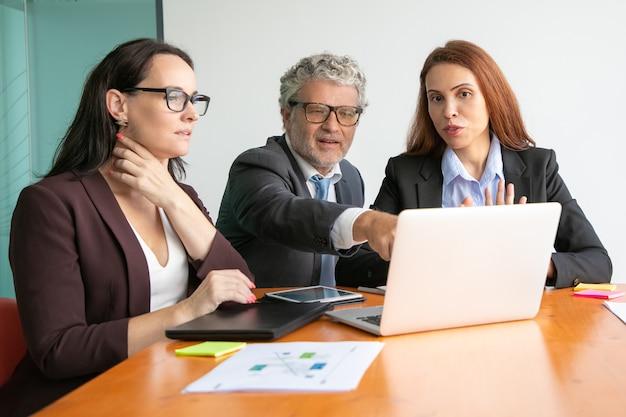 ノートパソコンでのプレゼンテーションを見て議論するビジネス人々、ディスプレイを見て指さすビジネスマン 無料写真