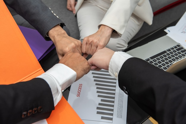 Business people with fist bump together in teamwork at the office above desk with document. Premium Photo