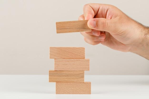 Concetto di pianificazione aziendale sulla vista laterale del backgroud bianco. mano posizionando il blocco di legno sulla torre. Foto Gratuite