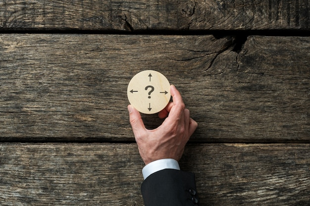 Business planning and decision conceptual image - businessman holding wooden cut circle with question mark and arrows pointing in different directions on it. Premium Photo