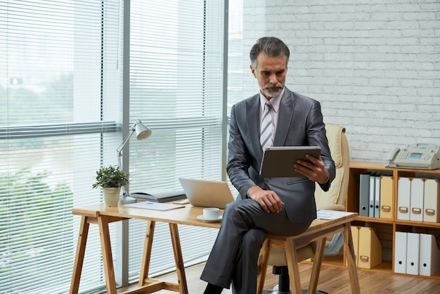 Business professional working with digital tablet in his eco-friendly office seated on the wooden desk Free Photo