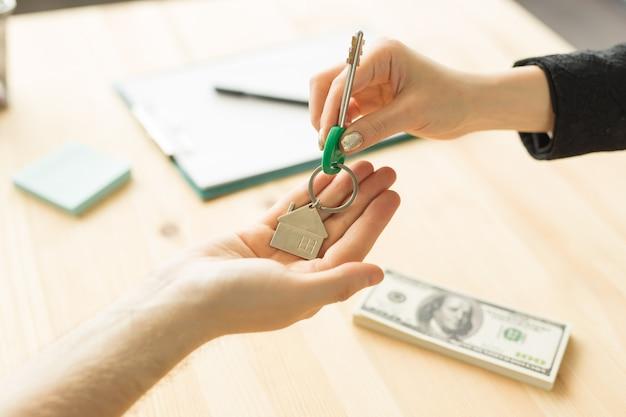 Концепция бизнеса, риэлтора и недвижимости - ключи из рук в руки от нового дома. Premium Фотографии