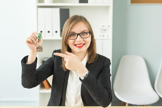 비즈니스, 부동산 중개인 및 부동산 개념-키를 들고 매력적인 웃는 여자의 초상화 프리미엄 사진