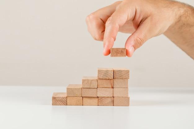Concetto della gestione dei rischi e di affari sulla vista laterale del backgroud bianco. uomo d'affari ponendo blocco di legno sulla torre. Foto Gratuite