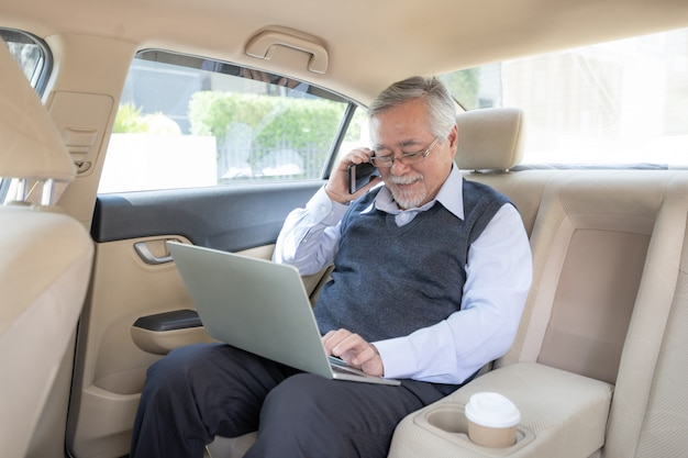Business senior rich man stock trader working with laptop computer using a smart phone Premium Photo