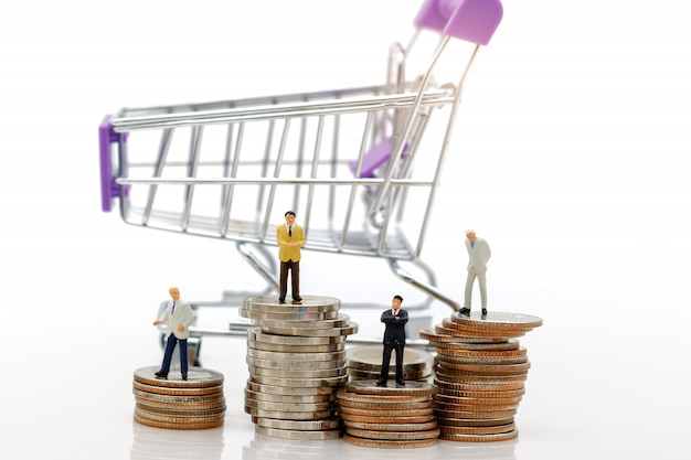 Business standing on stack of coins with shopping cart. Premium Photo