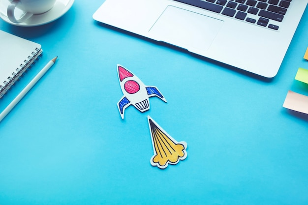 Business start up concept with rocket on desk table color Premium Photo