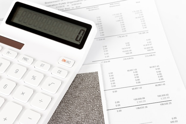 Business startup analysis summary report and using a calculator to calculate the numbers. Premium Photo