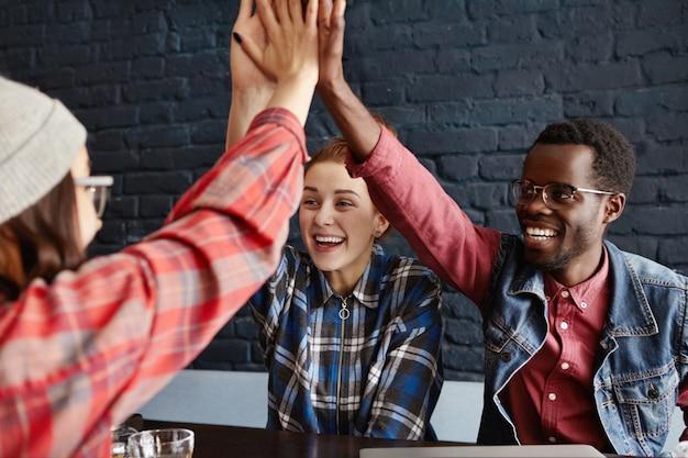 ビジネス、スタートアップ、チームワーク。カフェでの成功を祝う、カジュアルな服装で起業家の幸せで熱狂的なクリエイティブチームがお互いにハイタッチをしている 無料写真