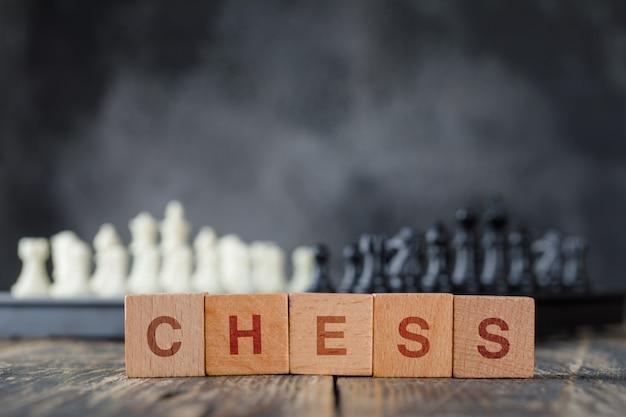 チェス盤と数字、霧と木製のテーブルの側面に木製キューブのビジネス戦略コンセプト。 無料写真