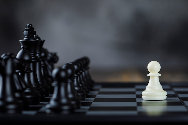 Business strategy concept with figures on chessboard on foggy and wooden table side view. Free Photo