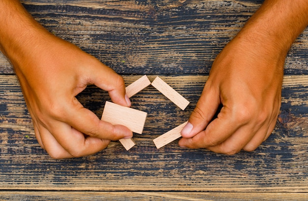 Business strategy concept on wooden background flat lay. hand holding wooden blocks. Free Photo