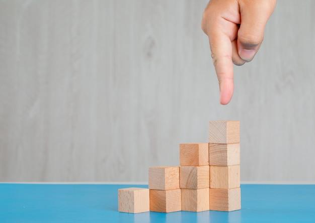Concetto di successo di affari sulla vista laterale della tavola blu e grigia. pila di dito mostrando cubi di legno. Foto Gratuite