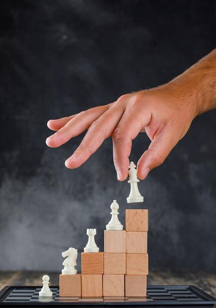 Concetto di successo di affari con la vista laterale della scacchiera. uomo posizionando la figura sulla piramide di blocchi. Foto Gratuite