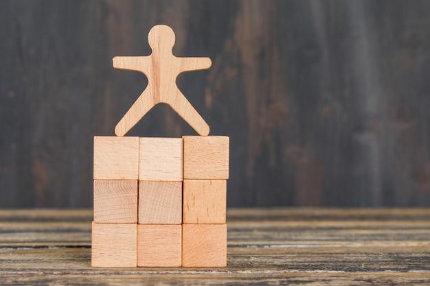 Concetto di successo di affari con il modello umano sui cubi di legno sulla vista laterale della tavola di legno. Foto Gratuite
