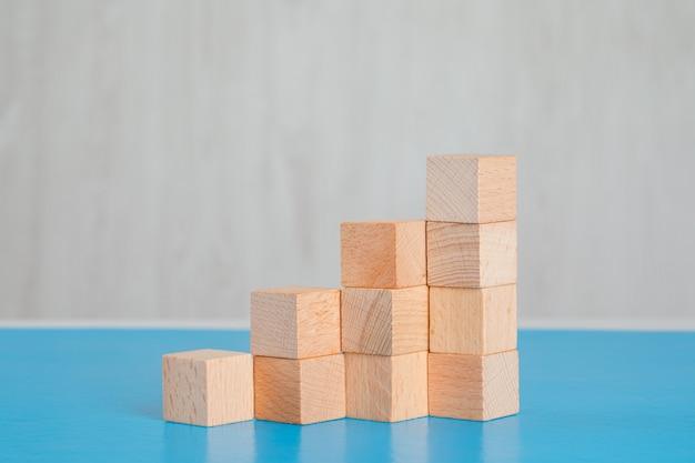 Concetto di successo di affari con la pila di cubi di legno sulla vista laterale della tavola blu e grigia. Foto Gratuite