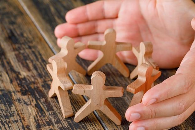 Concetto di successo di affari sulla vista di legno del piano d'appoggio. mani che proteggono figure in legno di persone. Foto Gratuite