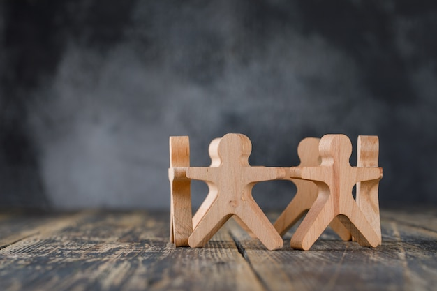 Business success and teamwork concept with wooden figures of people side view. Free Photo
