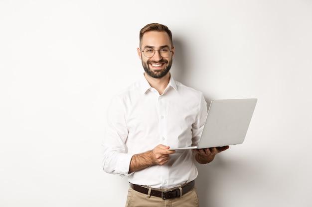 사업. 노트북, 컴퓨터를 사용하고 웃고, 서있는 성공적인 사업가 무료 사진
