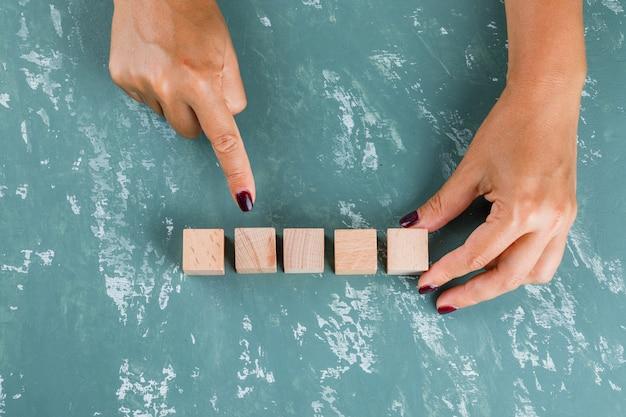 ビジネスターゲットコンセプト。女性を示すと木製のキューブを保持しています。 無料写真