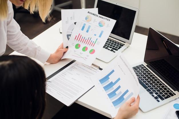 Бизнес-команда анализирует диаграммы и графики доходов с помощью современного ноутбука Premium Фотографии