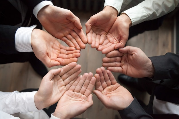 Business team join hands in circle palms up, growth concept Free Photo