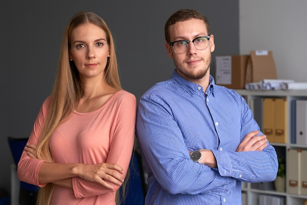 Business team standing shoulder to shoulder arms folded Free Photo