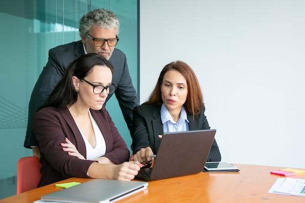 ノートパソコンでプレゼンテーションを見て、ディスプレイを指して、詳細を議論するビジネスチーム 無料写真