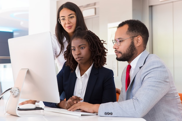 Business team watching project presentation on desktop together Free Photo